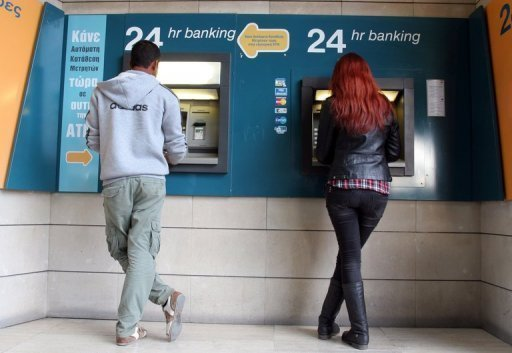A man and a woman withdraw money from cash-points in Nicosia. Cyprus turns to Russia as President Nicos Anastasiades battles to garner support from lawmakers for a controversial eurozone bailout deal that the central bank warned was in danger of collapse