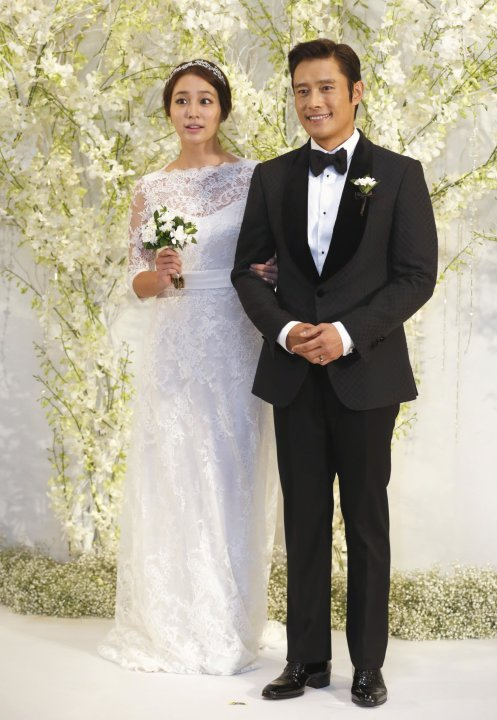 South Korean actor Lee poses with his bride during a photo call before their wedding ceremony in Seoul