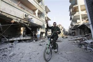 A Shi'ite fighter rides his bicycle on a damaged street …