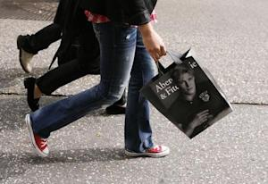 A shopper walks down Fifth Avenue with an Abercrombie…