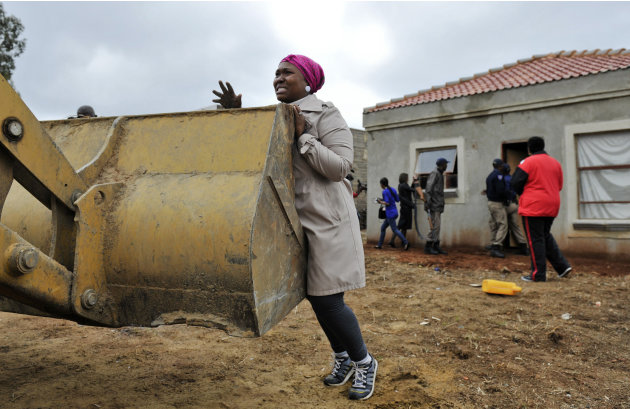 An unidentified woman unsuccessfully tries to prevent workers from demolishing her home in Lenasia, south of Johannesburg, South Africa, Friday, Nov. 9, 2012. South African police have supervised the