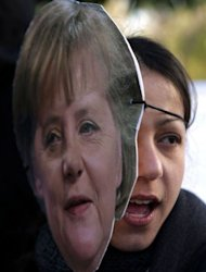 """A woman wearing a mask of German Chancellor Angela Merkel takes part in a protest against an EU bailout deal outside parliament in Nicosia on March 18, 2013. """"Wake up, they are sucking our blood,"""" protesters said during the demonstration"""