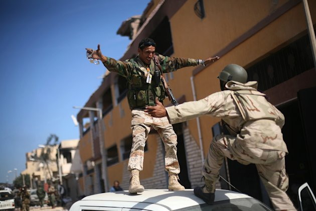 Revolutionary fighters celebrate the capture of Sirte, Libya, Thursday, Oct. 20, 2011. Officials in Libya's transitional government said Moammar Gadhafi was captured and possibly killed Thursday when