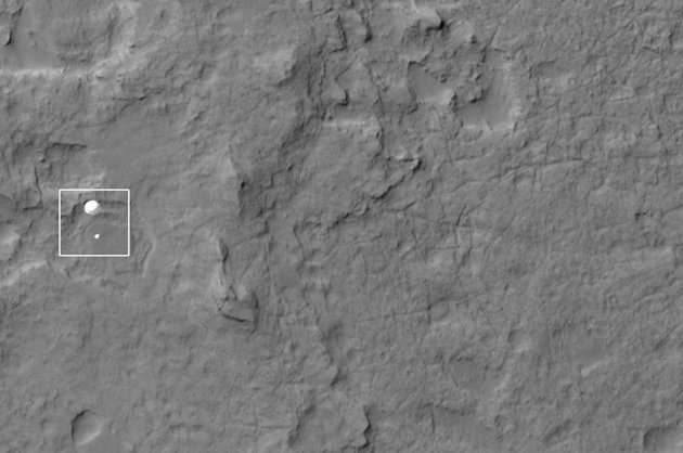 In this photo released by NASA/JPL-Caltech/Univ. of Arizona, NASA's Curiosity rover and its parachute, left, descend to the Martian surface on Sunday, Aug. 5, 2012. The high-resolution Imaging Science