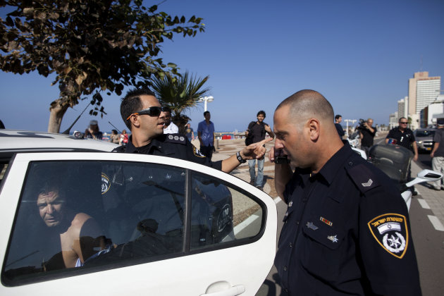 Israeli police officers detain a man who attacked a security guard at the U.S. embassy in Tel Aviv, Israel, Tuesday, Nov. 20, 2012. A knife and ax-wielding Israeli man attacked and lightly wounded a security guard at the U.S. Embassy in Tel Aviv on Tuesday before he was apprehended at the scene, police said. Israeli police spokesman said the man's motive was unknown, but political motives were not suspected and the incident had nothing to do with Israel's battle with Hamas militants in Gaza.(AP Photo/Oded Balilty)