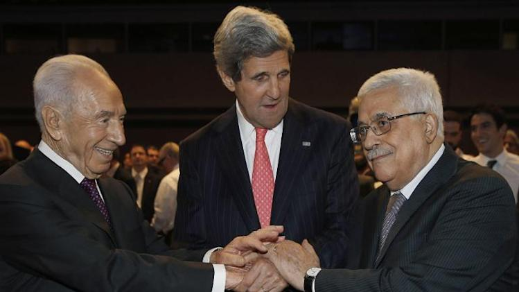 US Secretary of State John Kerry (centre) shakes hands with Israeli President Shimon Peres (left) and his Palestinian counterpart Mahmud Abbas at the King Hussein Convention Centre, at the Dead Sea, on May 26, 2013