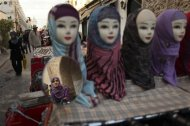 A Libyan woman is reflected in a mirror as she looks at headscarves displayed on plastic models at a market stall in central Tripoli in this November 28, 2011 file photo.     REUTERS/Mohammed Salem/Files