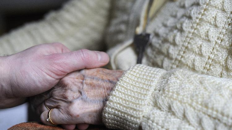 A woman suffering from Alzheimer's disease holds the hand of a relative