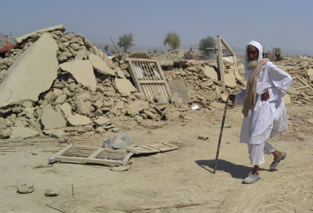 Survivor of earthquake walks near rubble of a mud house after it collapsed following the quake in the town of Awaran