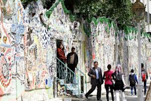 Syrians walk through a decorated wall that won the …