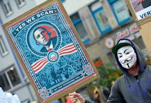 A protestor wearing a Guy-Fawkes-mask holds a banner…