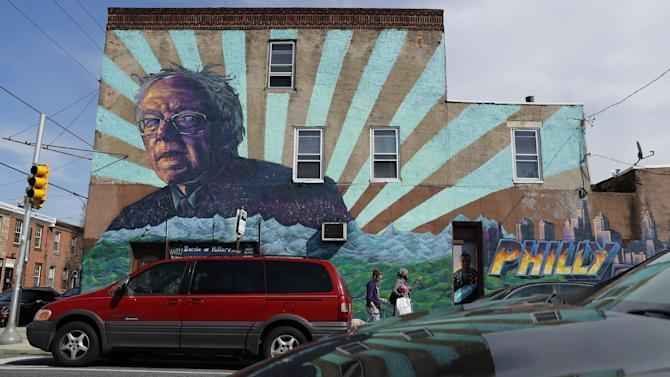 People walk past a mural of Democratic presidential candidate Bernie Sanders, Wednesday, March 23, 2016, in Philadelphia. Officials say they erred in issuing a violation to the building owner over the mural. Philly.com reports the city Department of Licenses and Inspections said Tuesday that the mural of the Vermont senator is political speech, not an advertisement, so the mural can stay. (AP Photo/Matt Slocum)