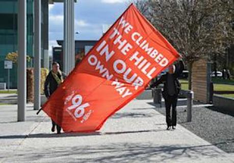 """Men hold a banner reading """"We climbed the hill…"""