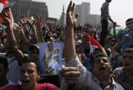 Egyptian protesters chant anti-military slogans, one carrying a photoshopped picture depicting the head of the ruling military council, Field Marshal Hussein Tantawi and ousted President Hosni Mubarak during a rally protesting the outcome of Mubarak's trial at Tahrir Square, Cairo, Egypt Tuesday, June 5, 2012. Egyptian lawmakers say the ruling military council has given them 48 hours to finalize the formation of a 100-member panel tasked to write the country's new constitution, or it will come up with its own blueprint for the body. (AP Photo/Nasser Nasser)
