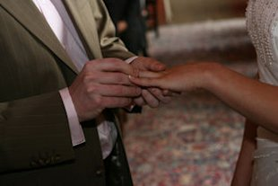 man placing ring on wife's finger