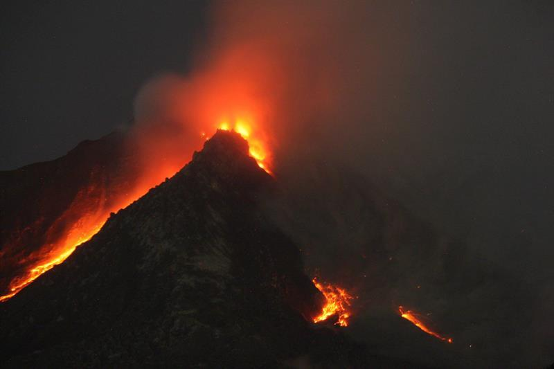 DED92. Karo (Indonesia), 14/06/2015.- Mount Sinabung spews hot gas and lava as seen from Tiga Serangkai village in Karo, North Sumatra, Indonesia, 14 June 2015. More than 2,700 people were moved from their homes near a volcano on Indonesia's Sumatra island on 04 June following a sharp increase in volcanic activity, an official said. The alert for Mount Sinabung was raised to the highest level as authorities fear that its growing lava dome could collapse any time. Mount Sinabung has erupted intermittently since late 2013. Sixteen people were killed and tens of thousands were temporarily displaced during an intense period of eruptions early last year. Nearly 2,000 people are still living in temporary shelters as a result of last year's eruptions. Others either returned to their homes or were relocated elsewhere. EFE/EPA/DEDI SAHPUTRA