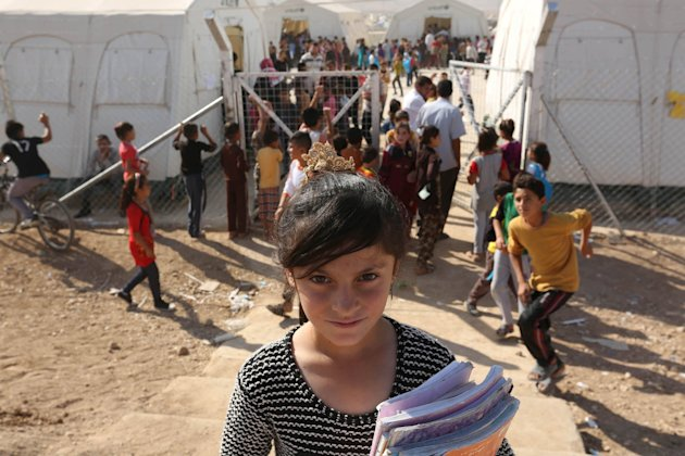 CLICK IMAGE for slideshow: A Yazidi refugee girl from the minority Yazidi sect poses for a photograph on the first day of the new school term at Shary...