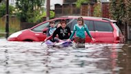 Youngsters make their way in a boat along a flooded road in Felpham near Bognor Regis, West Sussex, during last month's downpours