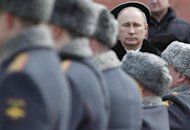 Russian President Vladimir Putin (R) attends a wreath laying ceremony to mark the Defender of the Fatherland Day in Moscow February 23, 2013. REUTERS/Maxim Shemetov
