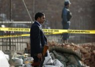 Afghan security personnel stand at the site of a suicide attack in Kabul November 21, 2012. REUTERS/Mohammad Ismail
