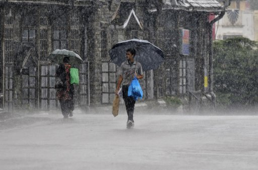 People hold umbrellas as they walk in heavy rain in Shimla