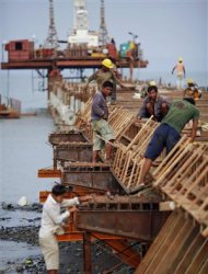 Workers from Indian conglomerate Essar Group construct a new port in Sittwe May 19, 2012. In northwest Myanmar, where the Kaladan River flows out into the Bay of Bengal, the two giant arms of a half-built wharf enfold the estuarine mud with steel and concrete. Their embrace is fraternal -- Myanmar's giant neighbor India is funding this new port in Sittwe, the capital of Rakhine State -- but also strategic. REUTERS/Damir Sagolj