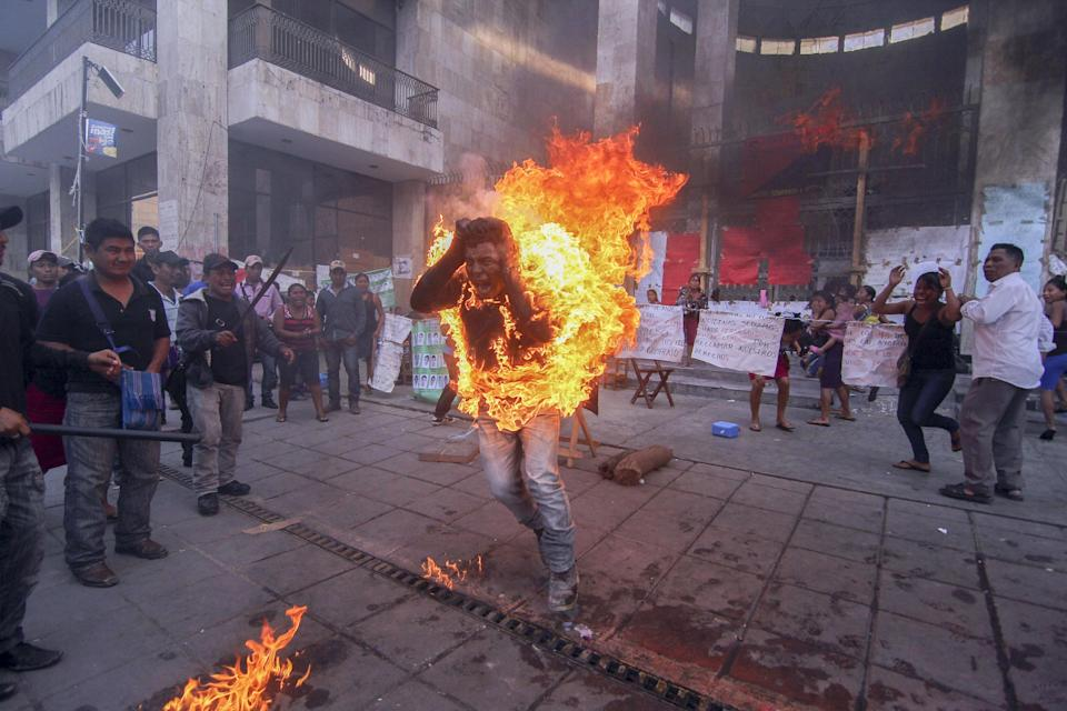 EDS. NOTE GRAPHIC CONTENT - Farmer Agustin Gomez Perez, 21, runs engulfed in flames after he was lit on fire as a form of protest outside the Chiapas ...