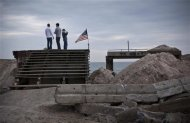 Three volunteers stand on the remains of the infrastructure of the Rockaway Beach boardwalk, which was destroyed by Hurricane Sandy on October 29, in the Rockaway Beach neighborhood of Queens, New York, November 10, 2012. New York Mayor Michael Bloomberg announced that the day would be a day of service, with volunteers being bused to various neighborhoods affected by Hurricane Sandy to help continue the clean up process. REUTERS/Andrew Burton