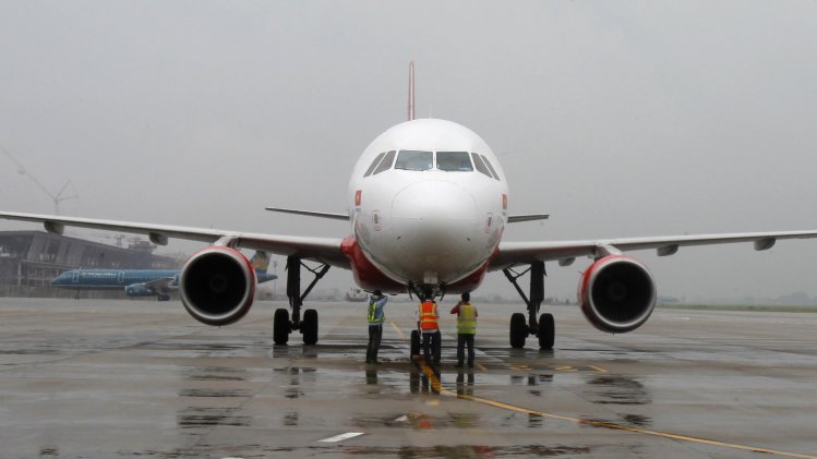Ground staff check a VietJet A320 airplane before departure for Bangkok at Noi Bai international airport in Hanoi