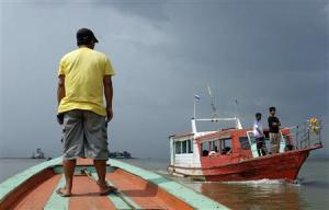 Men stand in boats crossing the invisible maritime…