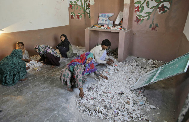 Hindus clean a temple after being attacked by a group of Muslim men in Karachi, Pakistan, Sunday, Sept. 30, 2012. A group of Muslims suspected of ransacking a Hindu temple in southern Pakistan may be charged with blasphemy, police said Sunday. The case is a rare twist on the use of the country's harsh blasphemy laws, which are more often invoked against supposed offenses to Islam as opposed to minority faiths. (AP Photo/Fareed Khan)