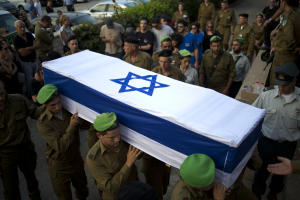 Israeli soldiers carry the coffin of 2nd Lt. Roy Peles,…