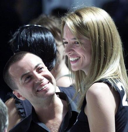 Top British designer Julien MacDonald (L) smiles as he looks up at Delphine Arnault (R) ahead of the..