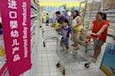 A family looks at foreign imported milk powder products at a supermarket in Beijing