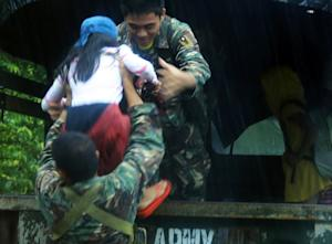 Military personnel evacuate residents from a village…