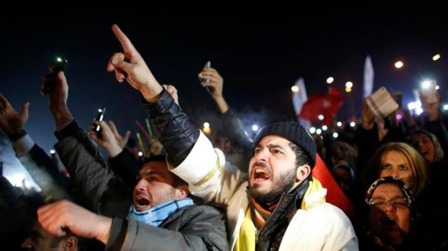 Supporters of Turkey's PM Erdogan shout slogans as they gather to welcome his arrival in Ankara