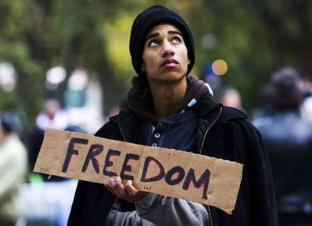 "A man holds a sign reading ""Freedom"" at St. James park makeshift headquarters for the ""Occupy Toronto"" movement in Toronto"