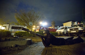 An armed police officer takes cover during a bout of…