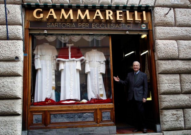 Annibale Gammarelli stands outside his family's tailor shop next to a display window showcasing Papal clothes (Reuters)
