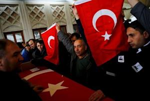 Men hold Turkish flags over the coffin of a car bombing …