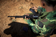 In this Jan. 31, 2013 photo, a Kachin Independence Army soldier cleans his rifle at an outpost on the Law Hpyu hilltop, one of the last hilltop outposts defending Laiza, where the guerrilla group's headquarters are located, in northern Myanmar's Kachin-controlled region. Kachin state is home to the last rebel insurgency left fighting in Myanmar that hasn't signed a cease-fire with President Thein Sein's government. Although the hills around Laiza have grown quiet for now, the dramatic upsurge in fighting underscored how far Myanmar is from achieving one of the things it needs most - a political settlement to end not just the war with the Kachin, but simmering conflicts with more than a dozen other rebel armies which have plagued the country for decades and still threaten its future. (AP Photo/Alexander F. Yuan)