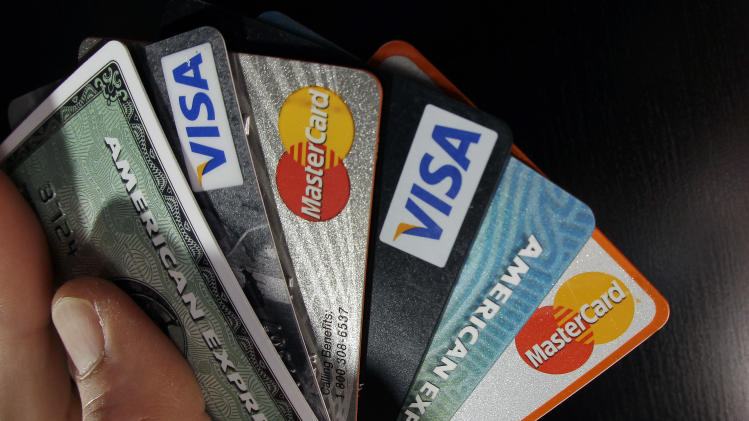 FILE - In this March 5, 2012 file photo, consumer credit cards are posed in North Andover, Mass. The rate of credit card payments at least 90 days overdue fell in the second quarter to the lowest level since 1994, according to credit reporting agency TransUnion. The findings are the latest sign that Americans are making paying their credit card accounts on time a priority. (AP Photo/Elise Amendola, File)