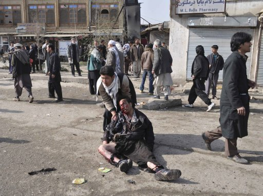 A wounded man is being helped after a suicide blast targeting a Shi'ite Muslim gathering in Kabul