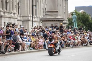 Spectators line the street as Harley riders participate …