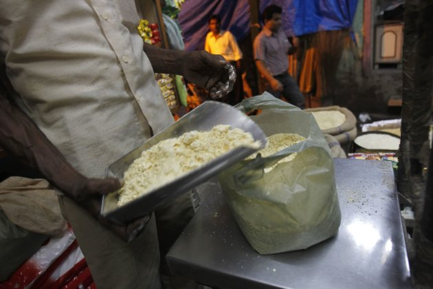 A salesman weighs chickpea flour for a customer inside a family-owned grocery store at a market in the old quarters of Delhi