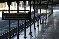 A cleaning woman is seen on the empty platform of the Athens central train station during a 48-hour nationwide general strike on Tuesday, Nov. 6, 2012. Greece's unions are holding their third general strike in six weeks in the hope of persuading politicians not to back a major new austerity program that will commit the country to further hardship. (AP Photo/Thanassis Stavrakis)