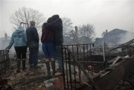 Residents look over the remains of burned homes in the Rockaways section of New York, October 30, 2012. REUTERS/Keith Bedford