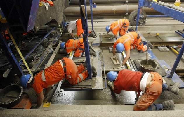 Workers use finishing trowels to plane fresh concrete on the track bed of the rails in the NEAT Gotthard Base tunnel near Erstfeld