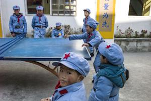 Children dressed in uniforms play table tennis during …