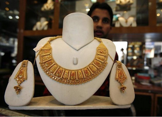 Shopkeeper displays gold jewellery inside his shop in Jammu